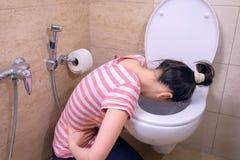 Den sjuka unga kvinnan spyr i toaletten som hemma sitter på golvet, tecknet för matförgiftning royaltyfria foton