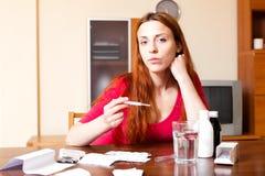 Den sjuka vanliga kvinnan ser vid termometern hemma Arkivfoton