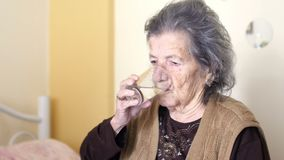 den sjukliga gamla kvinnan får preventivpillerar, drinkvatten stock video