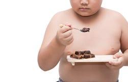 Den sjukligt feta feta pojken äter namachoklad som isoleras på vit royaltyfri bild