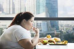 Den sjukligt feta kvinnan som äter fransman, steker i restaurangen royaltyfri foto