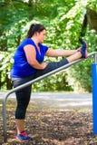 Den sjukligt feta kvinnan som gör sporten som utomhus sträcker i, parkerar arkivfoto