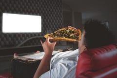 Den sjukligt feta mannen äter pizza framme av en TV på natten royaltyfria bilder