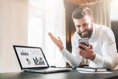 Den skäggiga affärsmannen i en vit skjorta sitter på en tabell framme av en bärbar dator med grafer, diagram, diagram på skärmen arkivbilder