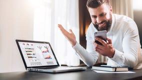 Den skäggiga affärsmannen i en vit skjorta sitter på en tabell framme av en bärbar dator med grafer, diagram, diagram på skärmen royaltyfri foto