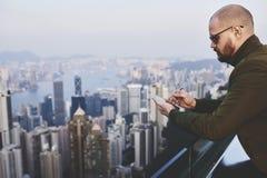 Den skäggiga affärsmannen kontrollerar mejl i nätverk via mobiltelefonen royaltyfri fotografi