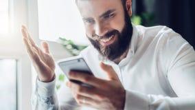 Den skäggiga affärsmannen sitter på tabellen och ser lyckligt på smartphoneskärmen som lyfter upp hans hand god nyheterna Royaltyfri Fotografi