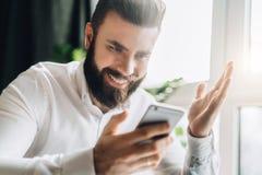 Den skäggiga affärsmannen sitter på tabellen och ser lyckligt på smartphoneskärmen som lyfter upp hans hand god nyheterna Fotografering för Bildbyråer