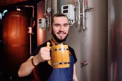 Den skäggiga attraktiva manliga bryggaren med träöl rånar i hand på bakgrund av bryggeriet arkivbilder