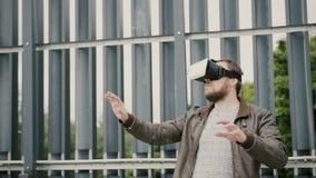 Den skäggiga attraktiva mannen använder virtuell verklighetexponeringsglas i det stads- utrymmet 4K arkivfoto