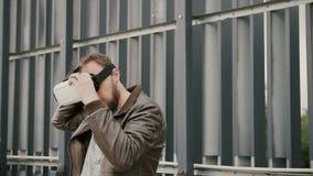 Den skäggiga attraktiva mannen använder virtuell verklighetexponeringsglas i det stads- utrymmet 4K royaltyfria foton