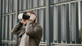 Den skäggiga attraktiva mannen använder virtuell verklighetexponeringsglas i det stads- utrymmet 4K Royaltyfri Bild
