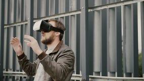 Den skäggiga attraktiva mannen använder virtuell verklighetexponeringsglas i det stads- utrymmet 4K Royaltyfri Fotografi