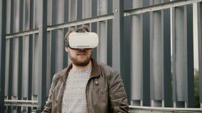 Den skäggiga attraktiva mannen använder virtuell verklighetexponeringsglas i det stads- utrymmet 4K Arkivfoton