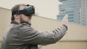 Den skäggiga attraktiva mannen använder virtuell verklighetexponeringsglas på taket 4K fotografering för bildbyråer
