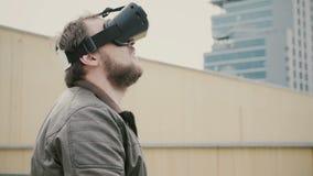 Den skäggiga attraktiva mannen använder virtuell verklighetexponeringsglas på taket 4K royaltyfri foto