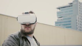 Den skäggiga attraktiva mannen använder virtuell verklighetexponeringsglas på taket 4K arkivbild