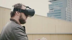 Den skäggiga attraktiva mannen använder virtuell verklighetexponeringsglas på taket 4K Royaltyfria Bilder