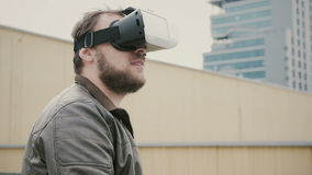 Den skäggiga attraktiva mannen använder virtuell verklighetexponeringsglas på taket 4K royaltyfri bild