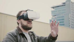 Den skäggiga attraktiva mannen använder virtuell verklighetexponeringsglas på taket 4K arkivfoto