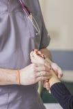 Den skäggiga doktorn som bär exponeringsglas, kontrollerar patientens puls Royaltyfri Foto