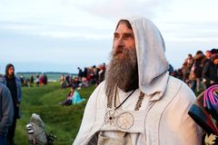 Den skäggiga druiden i ämbetsdräkter håller ögonen på solen att stiga på Stonehenge arkivbilder