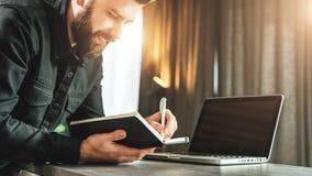 Den skäggiga le affärsmannen står av bärbara datorn som skriver i anteckningsbok Entreprenören analyserar information, jämför dat Royaltyfri Fotografi