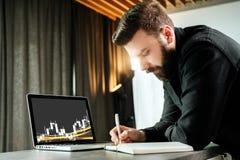 Den skäggiga le affärsmannen står av bärbara datorn som skriver i anteckningsbok Entreprenören analyserar information, jämför dat Royaltyfria Bilder