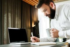 Den skäggiga le affärsmannen står av bärbara datorn som skriver i anteckningsbok Entreprenören analyserar information, jämför dat Arkivbilder
