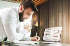 Den skäggiga le affärsmannen står av bärbara datorn som skriver i anteckningsbok Entreprenören analyserar information, jämför dat Arkivfoto