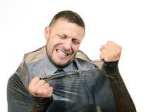 Den skäggiga mannen bryter plastpåsen Royaltyfri Bild