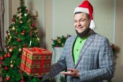 Den skäggiga mannen i en santa hatt rymmer gåvan i ask Royaltyfri Bild
