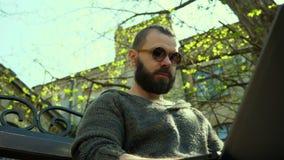 Den skäggiga mannen i solglasögon som skriver text på bärbara datorn lager videofilmer