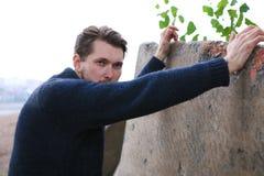 Den skäggiga mannen i tröja lutade på väggen Arkivbild