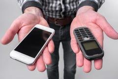 Den skäggiga mannen isolerade på en ljus bakgrund som rymmer en modern smartphone och en gammal mobiltelefon med knappar arkivfoto