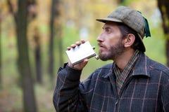 Den skäggiga mannen kommer med en flaska till hans mun i höstskogen Royaltyfri Bild