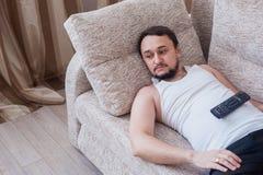 Den skäggiga mannen ligger på soffan med fjärrkontrollen Arkivbild