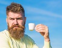Den skäggiga mannen med espresso rånar, drinkkaffe Mannen med skägget och mustaschen på strikt framsida dricker kaffe, blå himmel royaltyfri bild