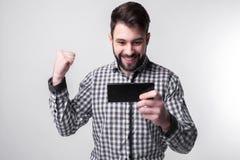 Den skäggiga mannen på upphetsande lekar för en vit bakgrund på smartphonen spelar Arkivfoto