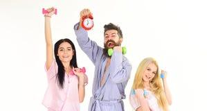 Den skäggiga mannen rymmer ringklockan Konditionlivsstilbegrepp Instruktören som är macho med attraktiva flickor, gör morgonövnin Arkivbild