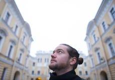 Den skäggiga mannen ser högväxta byggnader Royaltyfri Bild