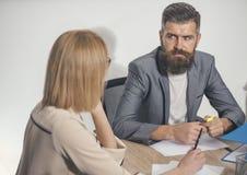 Den skäggiga mannen sitter på skrivbordet med kvinnan, baksidasikt Affärsmanarbete på affärsplan med affärskvinnan Man med skägge Royaltyfria Bilder