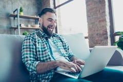 Den skäggiga mannen som använder att prata till och med internet wi-fi på bärbara datorn, sitter Arkivfoton