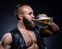 Den skäggiga mannen som dricker öl från ett öl, rånar arkivfoton