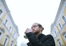 Den skäggiga mannen som dricker kaffe och ser byggnaden Arkivfoton