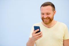 Den skäggiga mannen som ser in i telefonen, jublar fotoet för att annonsera mycket utrymme under texten Arkivfoto
