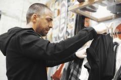 Den skäggiga mannen väljer kläder på shoppa royaltyfria bilder