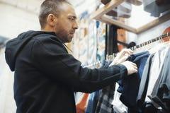 Den skäggiga mannen väljer T-tröja på shoppa royaltyfria bilder
