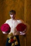 Den skäggiga muskulösa mannen med den sexiga kroppen rymmer den röda rosasken arkivfoton