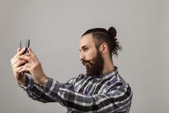 Den skäggiga stiliga mannen tar selfie vid telefonen i blått kvadrerat s Arkivbild